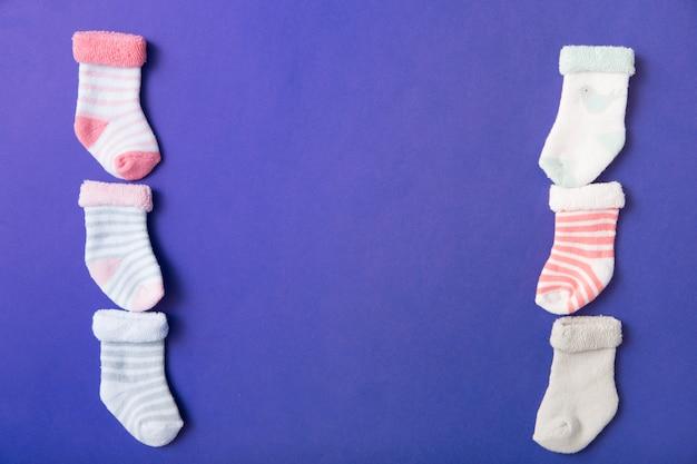 Rangée de nombreuses chaussettes pour bébé sur fond bleu Photo gratuit