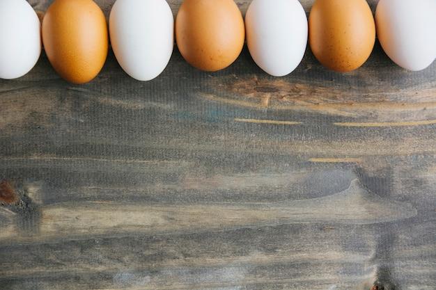 Rangée d'oeufs bruns et blancs sur fond en bois Photo gratuit