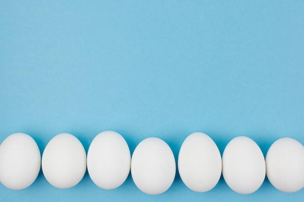Rangée d'oeufs de poule blanche sur la table bleue Photo gratuit