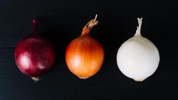 Rangée d'oignons colorés sur fond noir Photo gratuit