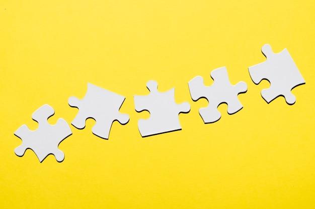 Rangée de pièce de puzzle blanche sur une surface jaune Photo gratuit