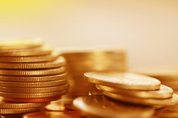 Rangée de pièces sur fond bois pour finances et concept d'épargne, investissement, couleur or Photo Premium