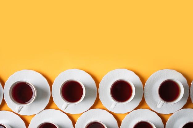 Rangée de tasse de thé blanc à base de plantes sur fond jaune Photo gratuit