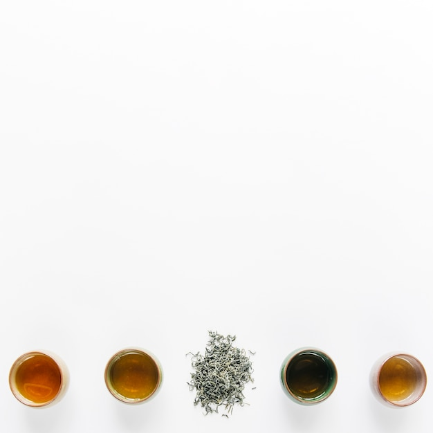 Rangée De Tasses à Thé à Base De Plantes Avec Des Feuilles Sèches Sur Fond Blanc Avec Espace De Copie Photo gratuit