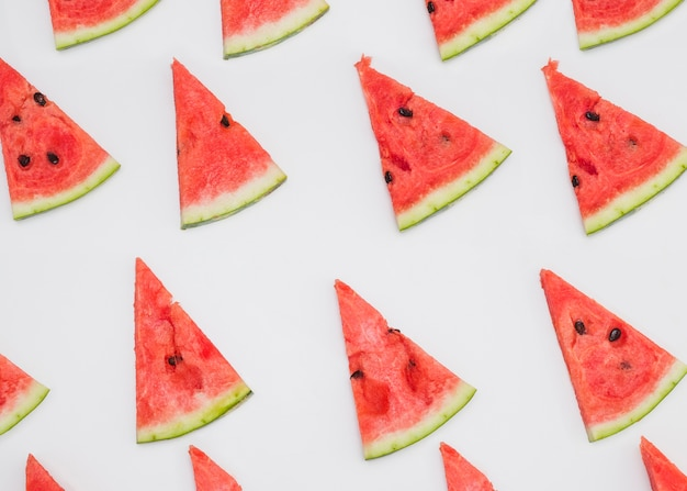 Rangée de tranches de melon d'eau triangulaires sur fond blanc Photo gratuit