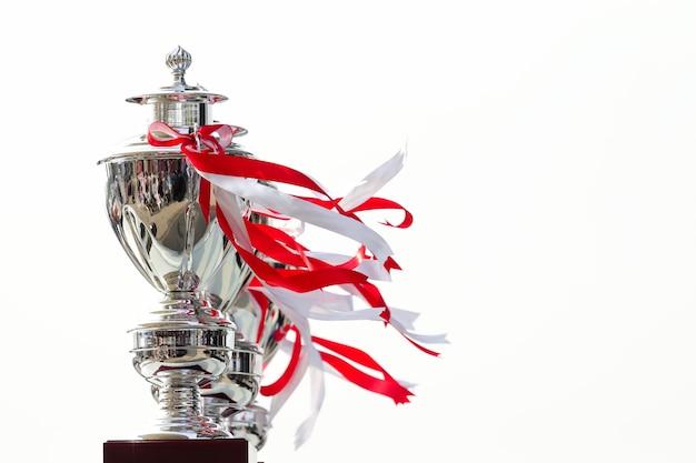 Rangée De Trophée De La Coupe à égalité Avec Ruban Blanc Et Rouge Sur Fond Blanc Photo Premium