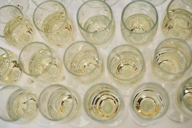 Rangée de verres remplis de champagne froid vin blanc table blanche Photo Premium