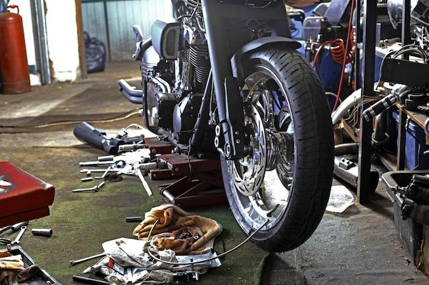 Rangée de vis et d'outils à clé sur un sol d'atelier près d'un vieux moteur de vélo ou de moto réparé. scène industrielle avec équipement Photo Premium