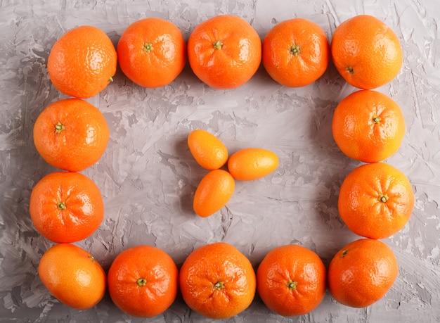 Rangées de mandarines formant un rectangle et trois kumquats à l'intérieur, vue de dessus. Photo Premium