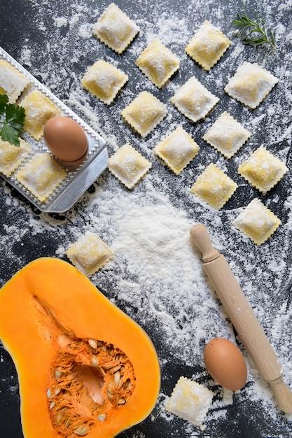 Rangées de raviolis crus de citrouilles avec des ingrédients, gros plan et vue de dessus Photo Premium