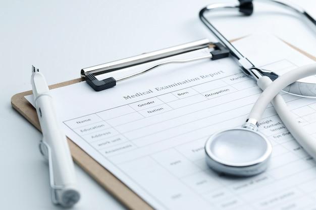 Rapport d'examen médical et stéthoscope sur un bureau blanc Photo gratuit