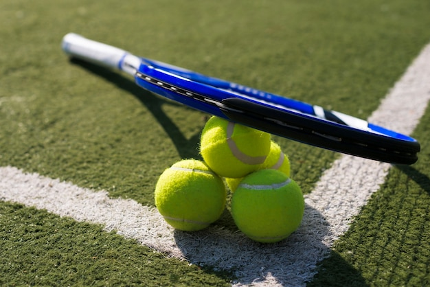 Raquette de tennis à angle élevé et balles au sol Photo gratuit