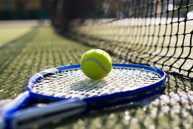 Raquette de tennis et balle au sol Photo gratuit