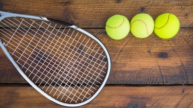 Raquette de tennis avec trois balles sur fond texturé en bois Photo gratuit