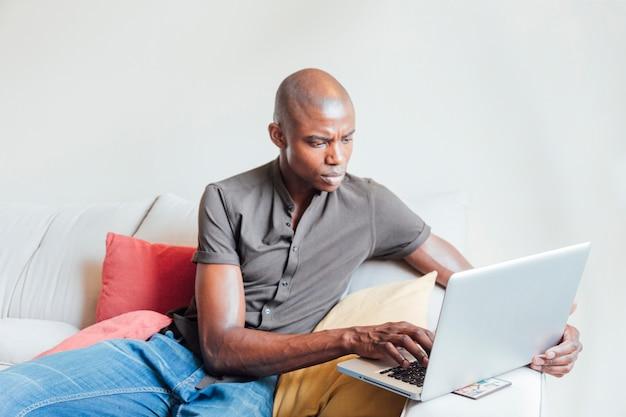 Rasé jeune homme africain assis sur un canapé à l'aide d'un ordinateur portable Photo gratuit