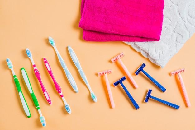 Rasoir en plastique avec brosses à dents et une serviette sur fond coloré Photo gratuit