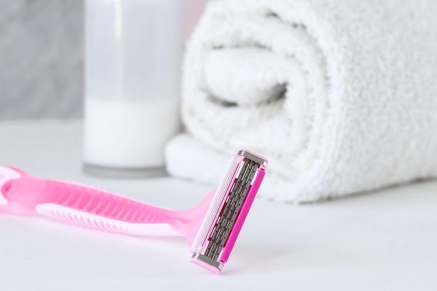 Rasoir pour femme avec shampoing, serviette et antisudorifique dans la salle de bain Photo Premium