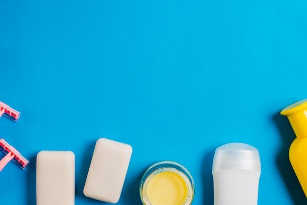 Le rasoir; savon; hydratant et bouteilles de shampoing sur fond bleu Photo gratuit