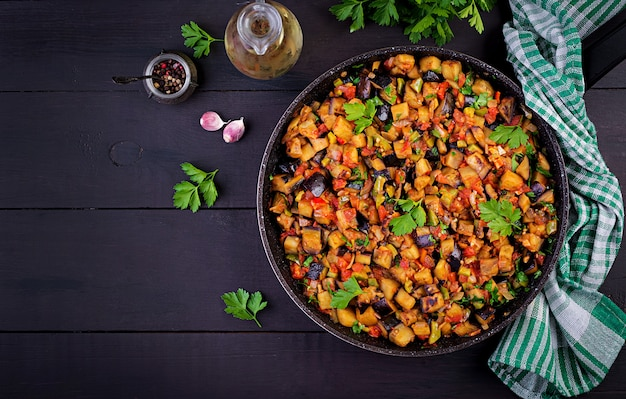 Ratatouille. aubergines de ragoût végétarien, poivrons, oignons, ail et tomates aux herbes Photo Premium