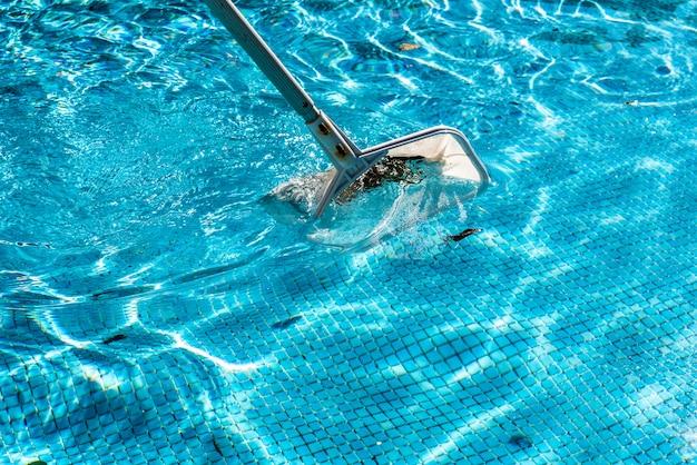 Râteau écumoire en forme de filet pour piscine en été. Photo Premium
