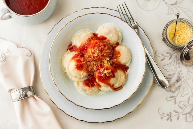 Ravioli aux sauces tomates et fromage râpé sur bol en céramique contre nappe Photo gratuit