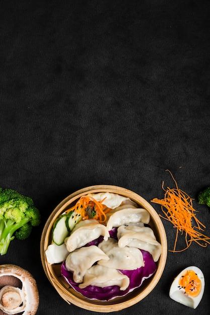 Raviolis chinois servis sur le traditionnel paquebot avec salade et œufs à la coque Photo gratuit