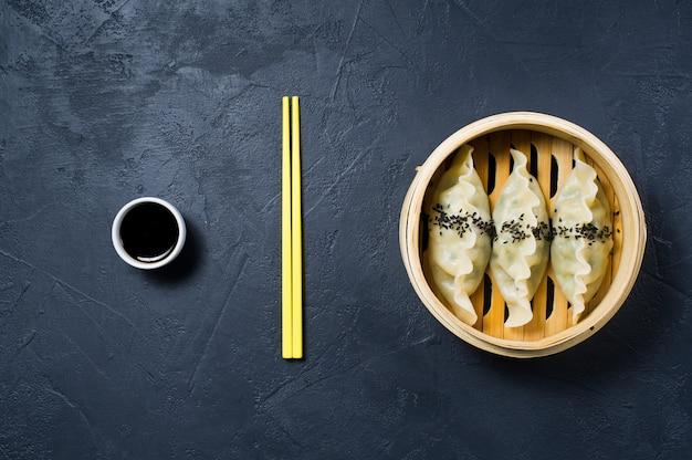 Raviolis coréens dans un steamer traditionnel, baguettes jaunes. Photo Premium