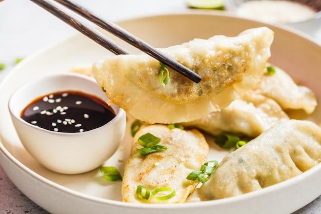 Raviolis coréens frits avec oignons verts et sauce sur une plaque blanche. Photo Premium