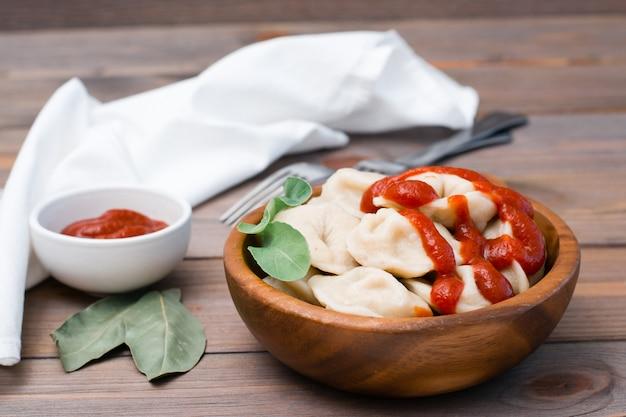 Raviolis cuits remplis de ketchup et de feuilles de roquette dans un bol en bois sur une table Photo Premium