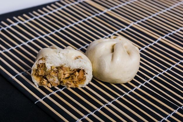 Raviolis Japonais à La Viande De Porc Sur Un Napperon Sur Fond Noir Photo gratuit