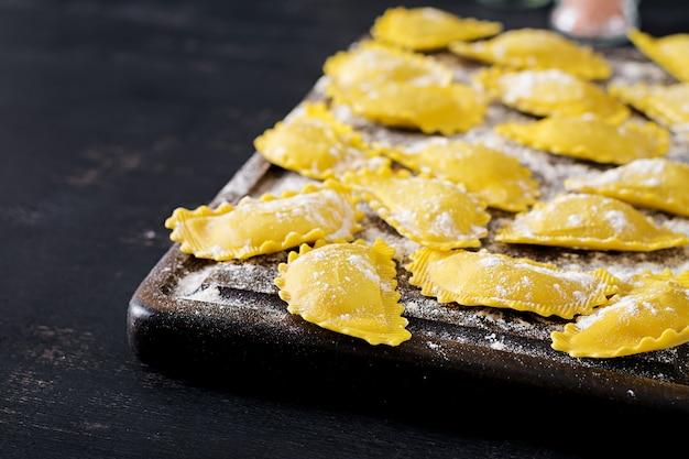 Raviolis non cuits sur la table. cuisine italienne. Photo Premium