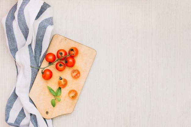Rayures serviette et tomates cerises sur une planche à découper sur la surface en bois Photo gratuit