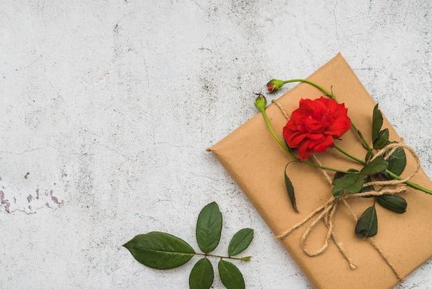 Re rose fleur sur une boîte cadeau enveloppée sur le vieux fond blanc Photo gratuit