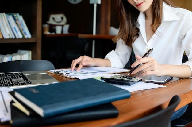 Recadré, coup, de, jeune femme, tenir stylo, et, utilisation, calculatrice, reposer, bureau Photo Premium