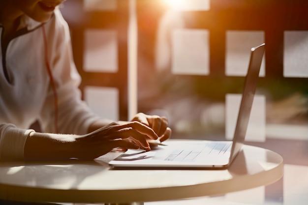 Recadré coup de main féminine en tapant sur son ordinateur portable au lieu de travail home studio Photo Premium