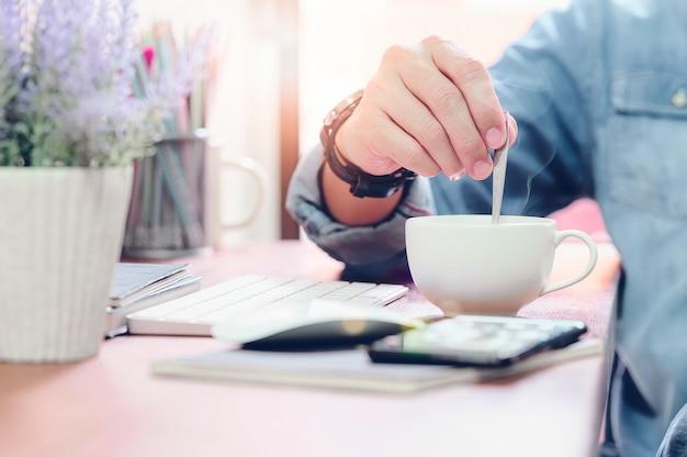 Recadré coup de main de l'homme tenant une cuillère tout en buvant un café chaud au café. Photo Premium