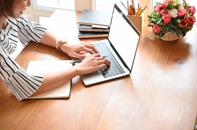 Recadré coup de secrétaire à l'aide de portable maquette sur une table en bois avec vue de dessus. Photo Premium