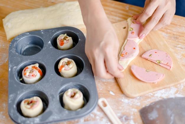 Recadrée main de femme préparant la pâte dans la plaque de cuisson Photo Premium