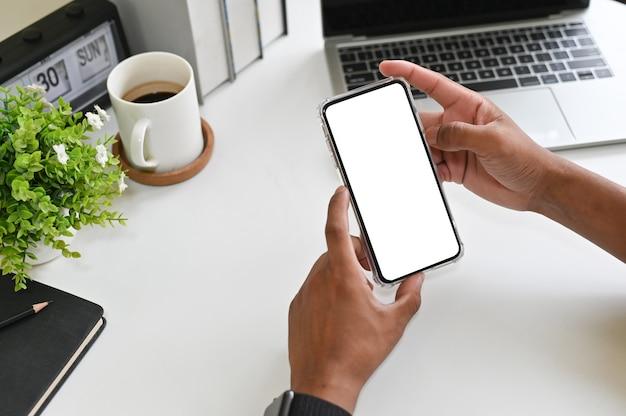 Recadrée des mains à l'aide de maquette smartphone sur le bureau avec un tracé de détourage. Photo Premium