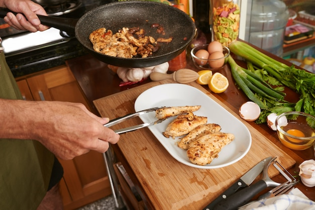 Recadrées de mains de cuisinier anonyme transférant de la viande frite avec une pince Photo gratuit