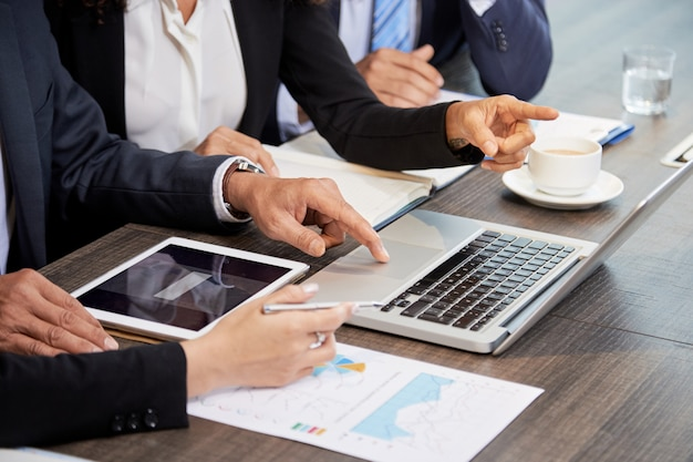 Recadrer des collègues à l'aide d'un ordinateur portable à la table Photo gratuit