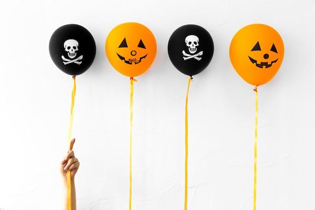 Recadrer la main avec de jolis ballons d'halloween Photo gratuit
