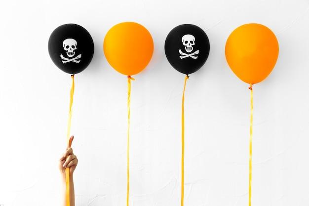 Recadrer la main près des ballons d'halloween Photo gratuit