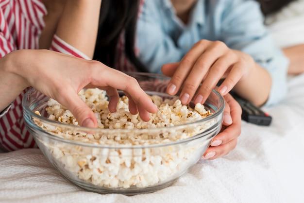 Recadrer les mains des femmes mangeant du maïs Photo gratuit