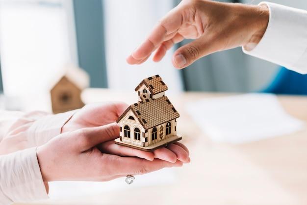 Recadrer les mains avec une petite maison Photo gratuit