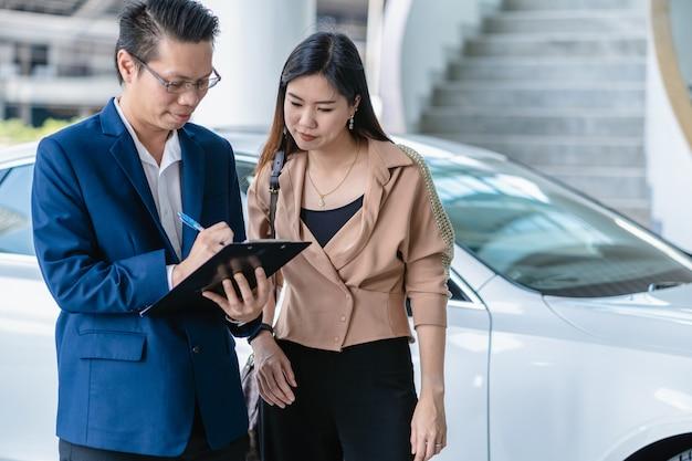 Réceptionniste asiatique vérifiant la liste des services de maintenance pour le client au centre de maintenance Photo Premium