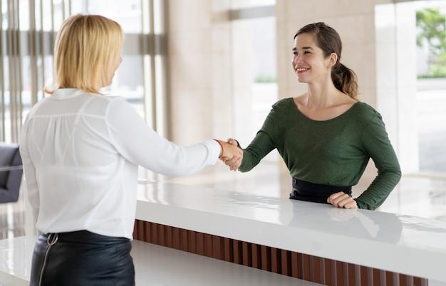 Réceptionniste de bureau accueillant une entreprise partenaire