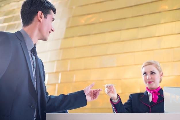 Réceptionniste de l'hôtel qui s'enregistre en donnant une carte-clé Photo Premium