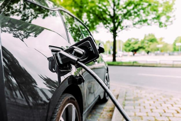 Recharge de voiture électrique moderne dans la rue. Photo Premium