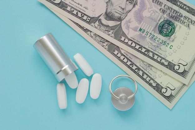 Récipient en métal pour les pilules et l'argent sur un fond bleu Photo Premium
